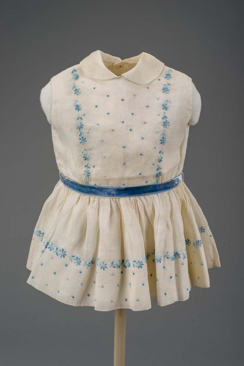 Girl's sleeveless sheer white (organdy) dress with small Peter Pan collar. Decorated at bodice and hem with blue embroidered dots and flowers; white cotton underslip edged with lace. Blue silk velvet ribbon belt. Three button holes closure up back, one button missing.  Tie belt of blue velvet ribbon which goes through two slender waist loops at side seams. - Boston MFA, public domain
