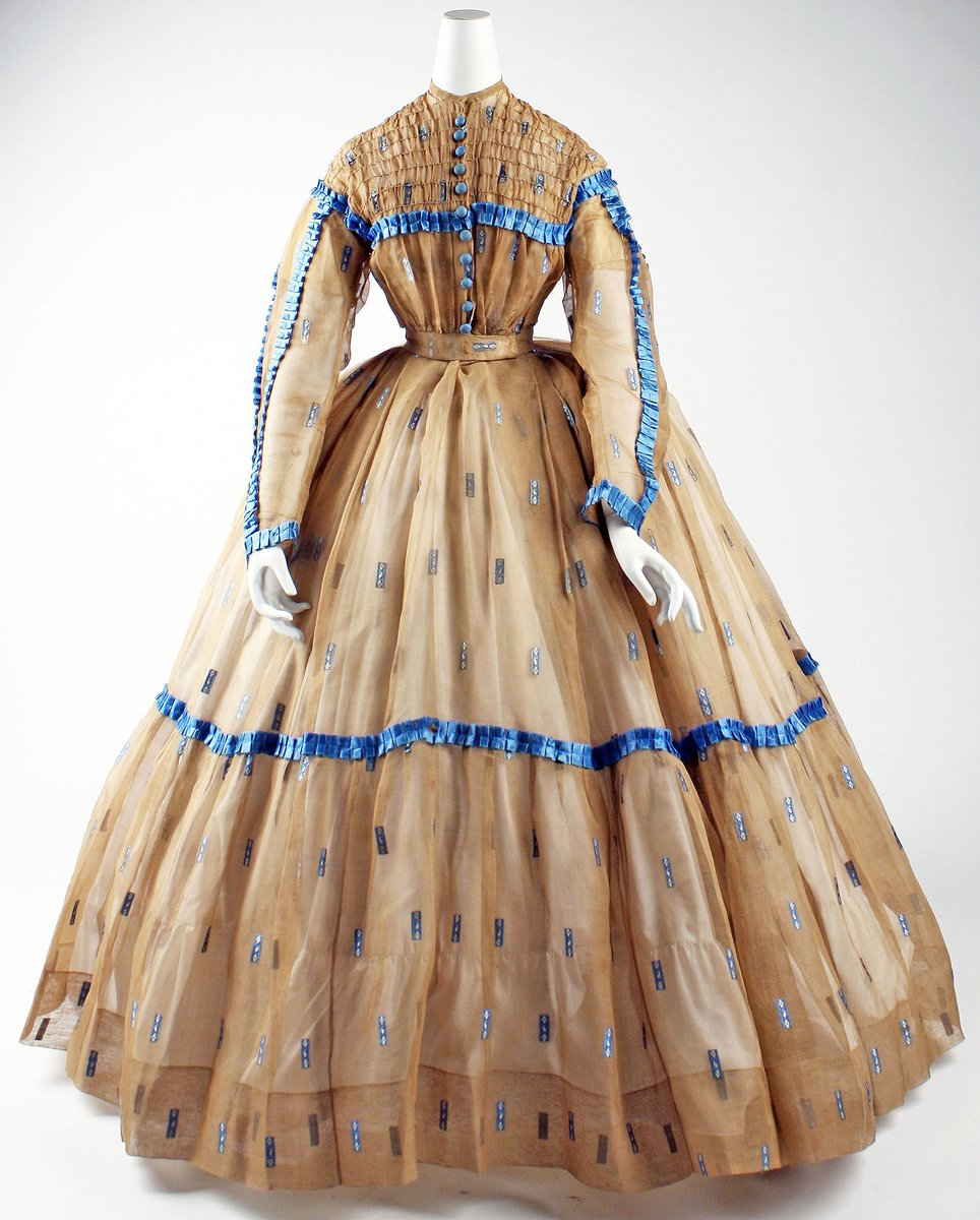 A smocked dress from the 1860s, tiny waist, long sleeves, long layers with contrasting blue satin ribbon. Big big skirts, layers.