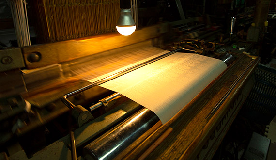 The loom on which the raw silk is woven, bathed in a golden light.