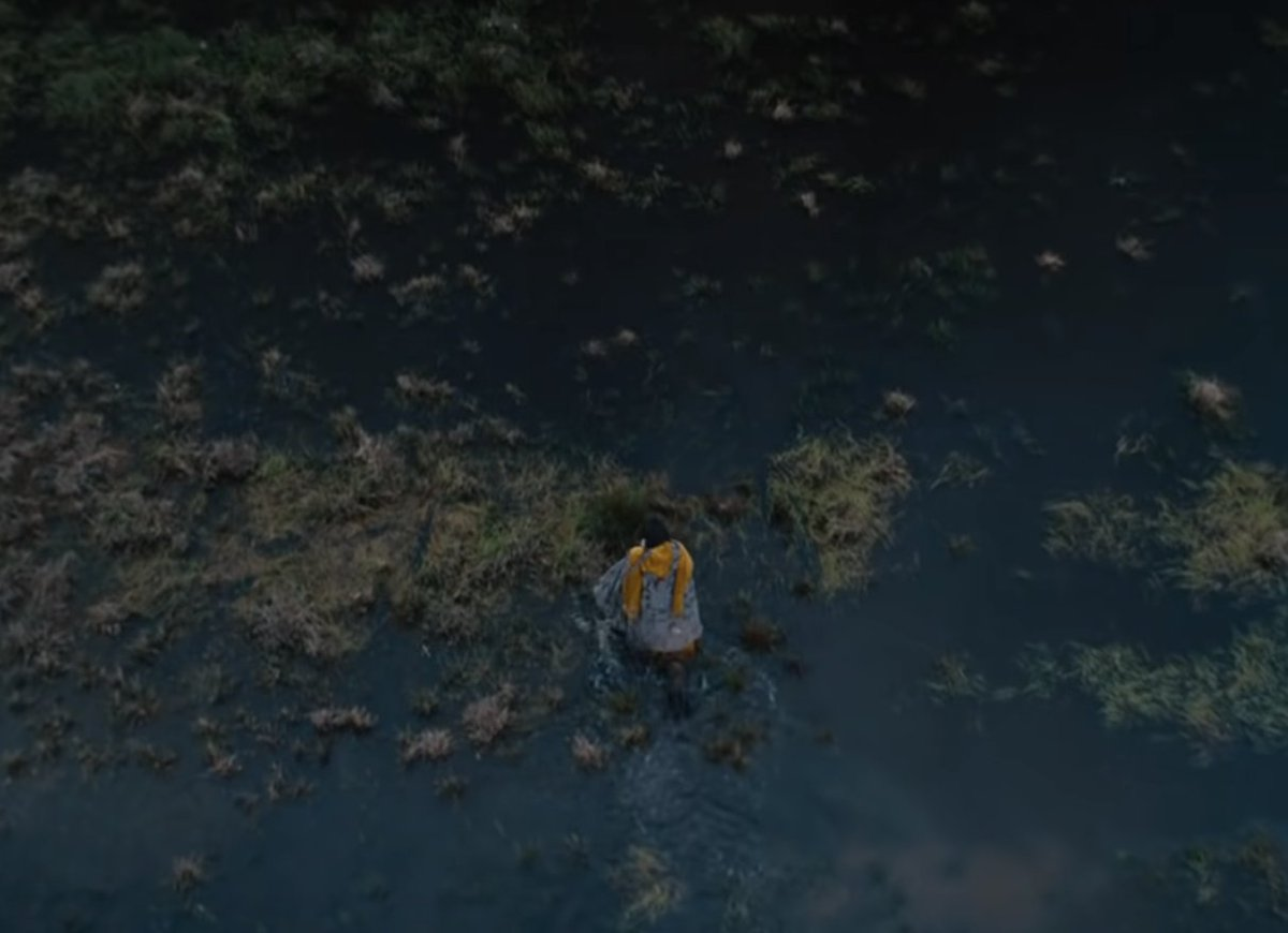 A figure walking across a bog, yellow cloak across shoulders. From The Green Knight.