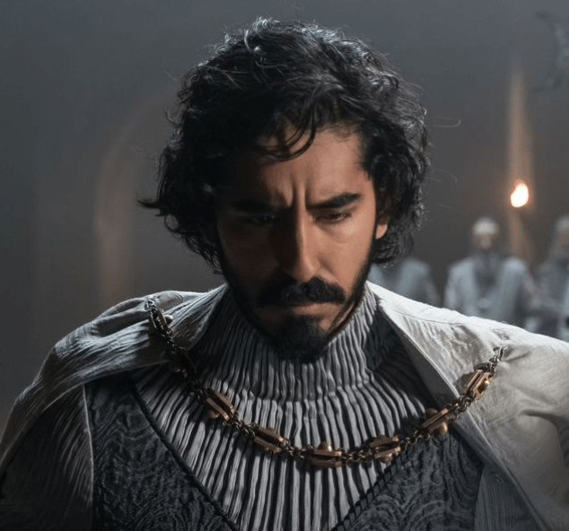 Dev Patel as Sir Gawain, looking down with a high-necked chained cape and chain, multiple textures in grey.