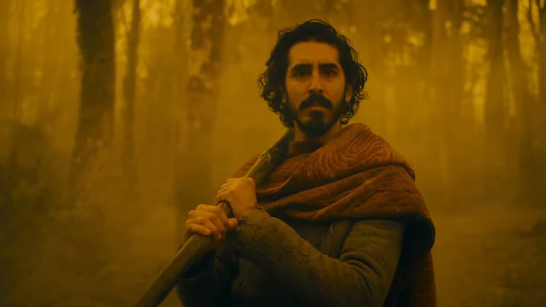 Dev Patel as Sir Gawain in The Green Knight fro A24 Films. A man with dark hair and a mustache holding an axe with a velvet stained cloak and trees in the background; all is washed in golden yellow.