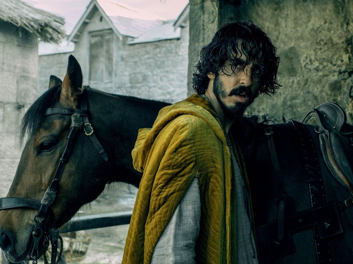 Dev Patel as Sir Gawain in The Green Knight by A24 Films in a yellow cloak of velvet, standing by a horse. He is by a stone building, the horse is brown. He is greasy-haired and scowling.