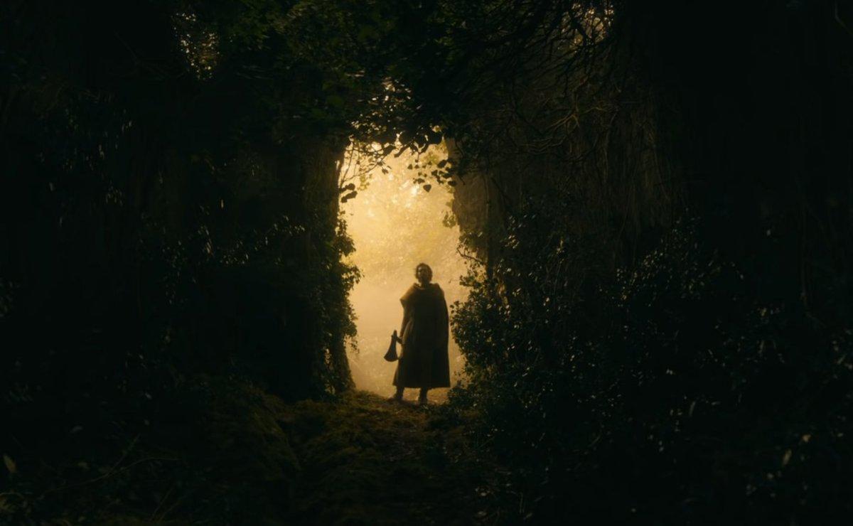 Gawain in a green doorway, lit in yellow, axe in hand (still wearing his yellow cloak)