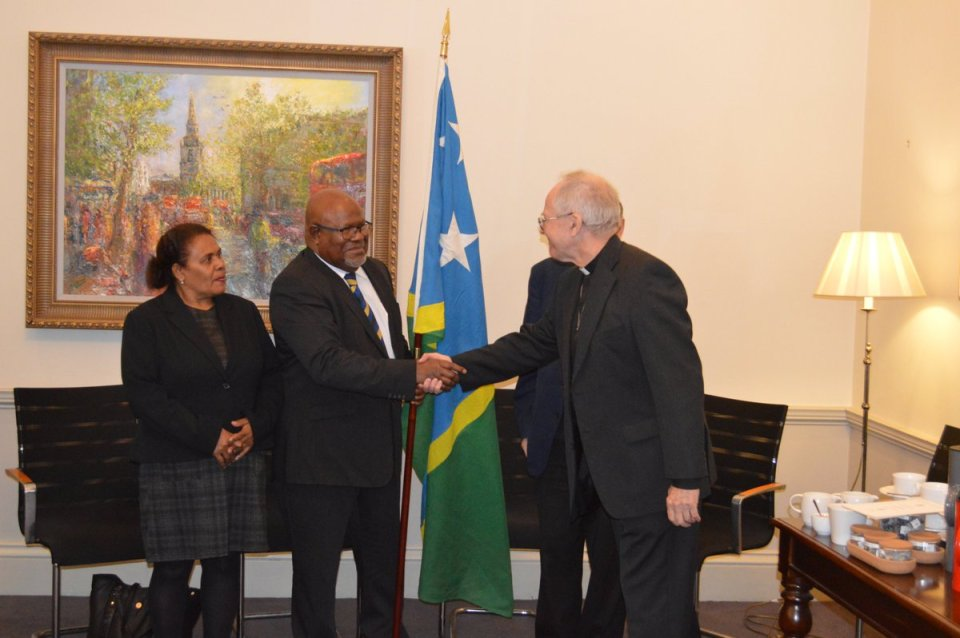 MMUK Trustee Canon John Pinder has presented His Excellency the Solomon Islands High Commissioner with the Solomon Islands flag which was present at Westminster Abbey during a thanks giving service to mark the Solomon Islands Independence on July 7th 1978.