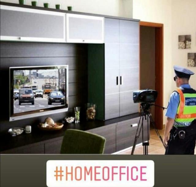 Homeoffice eines Polizisten, der im Wohnzimmer in Uniform eine Radarmessanlage auf den Fernseher ausgerichtet hat. Der TV-Sender zeigt fließenden Straßenverkehr.