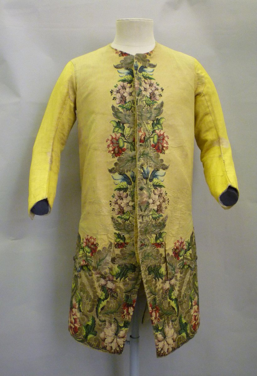 ©Victoria & Albert Museum, London- Man's waistcoat with a round neck, curving 2-piece sleeves, curved fronts and skirts reaching to between the top of the knee and mid-thigh. Each front has a pocket and pointed pocket flap. The fronts, back skirts, pocket flaps and cuffs are made of pale yellow silk taffeta with a chequered weave; the sleeves of yellow silk satin and the back pieced with yellow silk satin and yellow silk/linen. The waistcoat and sleeves are lined with linen twill; the skirts with ivory worsted, the linings of the pockets, pocket flaps and cuffs and front facings are ivory silk twill. The fronts are woven-to-shape with silver thread, frisé, strip and silk threads in white, black and shades of green red, pink, blue and purple, in a pattern of large flowers and leaves, along the front edges and hems. There is a seam at the waist of each front, where the woven pattern was cut, possibly to adjust for length. There are 17 worked buttonholes on a strip of the yellow taffeta.