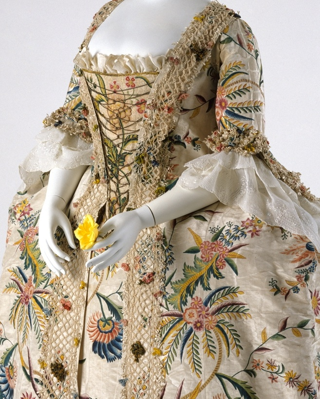 A perfect example of the robe à la française at mid-century, this hand-painted silk dress displays the opulence, Orientalism, and insatiable baroque excess of the time. Layers build on layers; flowers terrace out from the two-dimensional on the textile, to silk flowers, to nets laden with trapped flowers and floss. The silhouette is perfectly of the era: panniers dilate the hips; a narrow waist is achieved by the corset, which further pushes up and supports the bust. A deep décolletage is rendered more or less modest with insertions of bits of cloth, and the sleeves are finished with layers of engageants that are generally just basted in for easy detachment and washing and are thereby useful in keeping the valued dress clean. - via the Met