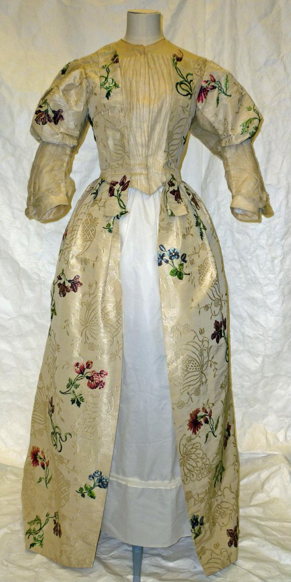 A woman's fancy dress of white figured silk, brocaded with floral motifs in coloured silks . The design of the silk shows isolated brocaded sprigs set against a tabby ground, elaborately patterned with a self-coloured flushing weft. The colours are reds and blues with emerald green leaves.    The garment was once a sack, probably made between 1755 and 1775. It was unpicked at some point and reconstructed for fancy dress. It is made of 4 widths of silk; some of the original 18c piecing remains, but the seams have all been resewn by machine. The bodice was resewn to a late 1890s pleated white cotton bodice. The sleeves are squares of silk sewn to long, gathered cotton muslin sleeves. © Victoria and Albert Museum