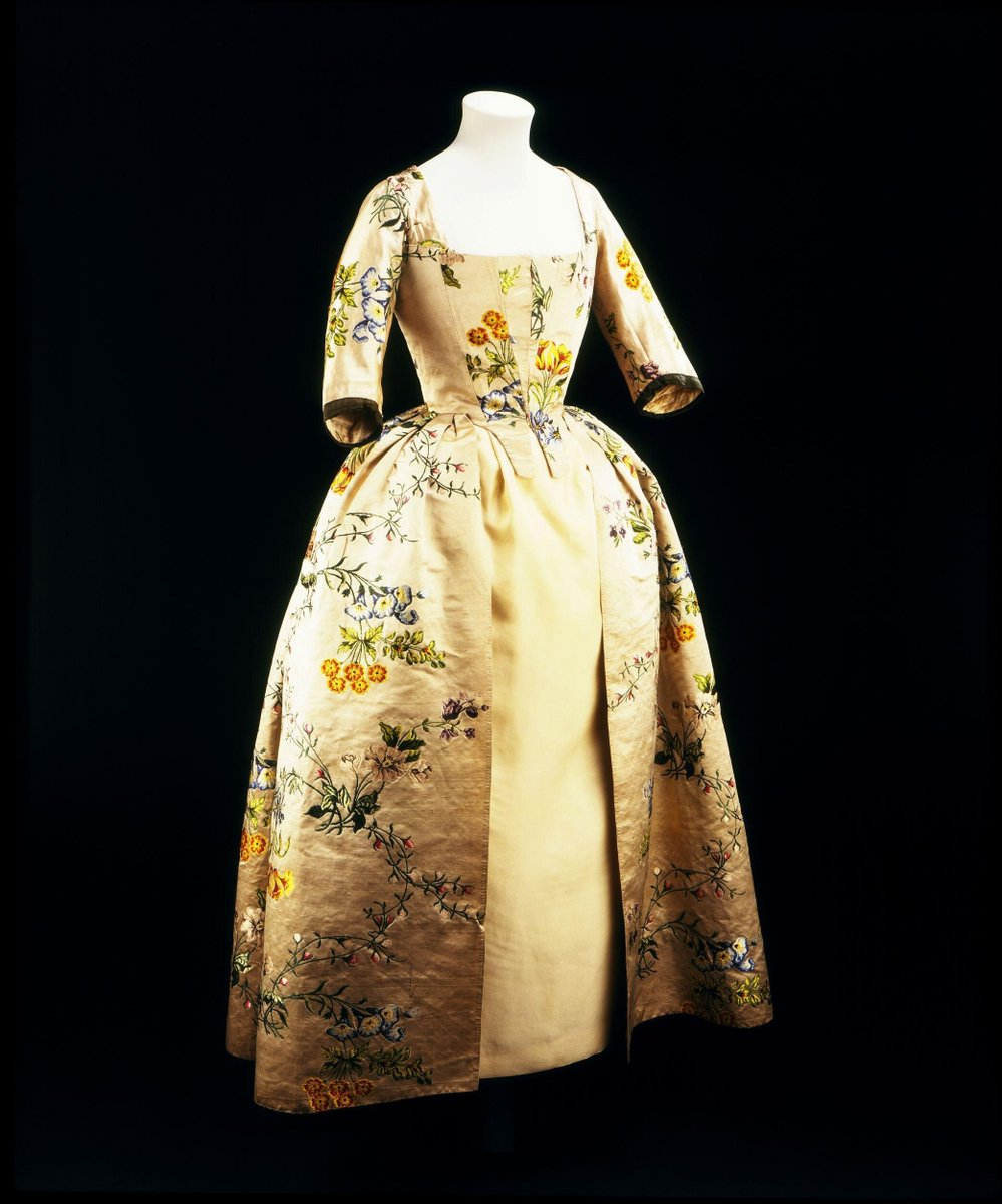©Victoria and Albert Museum, London - Gown of brocaded oyster coloured satin in coloured silks. Two large sprays flowers fill the width of the repeat, linked by upwards and downwards trails of bright pink berries and rose buds. From both sprays the flowers in upwards stems are brocaded in pink, fawn, lilac, white and black, while those hanging downwards are in shades of blue, yellow and red. Greens are used for the stems and leaves. The flowers are shaded in points rentrés.    Close-fronted bodice and an open fronted skirt with a fitted back. It was altered in the 1780s, and involved the back resetting of the skirt to give a concave waist seam, and removal of the cuffs and of the robings from the front of the bodice, which has been extended to meet in the centre front where it is now tied with three sets of ribbons. The ribbons are of red and green tobine with deckled edges. The sleeves are trimmed with lace.    Ground with a satin of 5 interruption of 2. The wefts of the brocaded desi