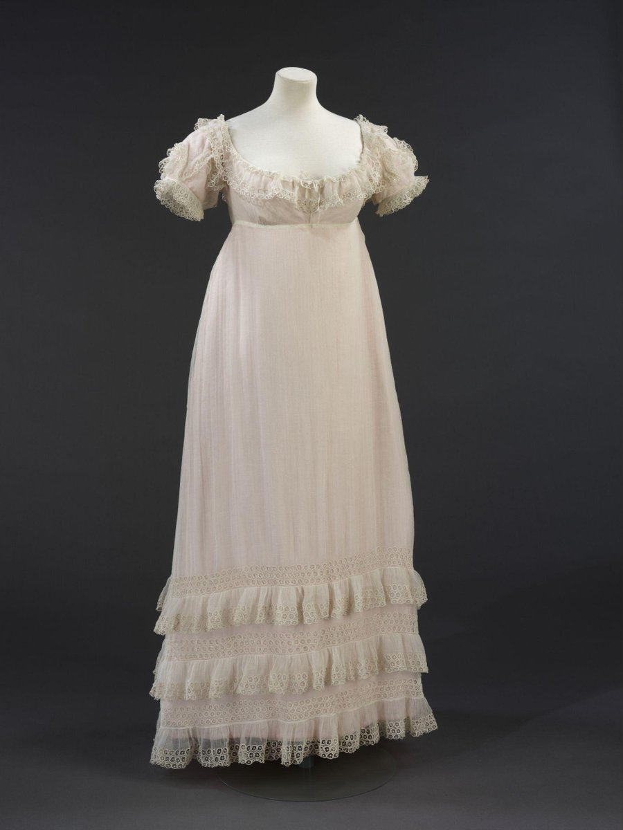 ©Victoria and Albert Museum, London - A white muslin evening gown with waistline under the bust, off-the-shoulder neckline and full, short sleeves. The back fastens at neck with cotton tape and narrow silk ribbon tie on a drawstring at the raised waist. The A-line skirt is about ankle-length and trimmed with three muslin flounces edged with whitework in a cutwork 'wheel' motif in buttonhole stitch and picot bars. A flounce worked in the same way adorns the neckline and sleeves.