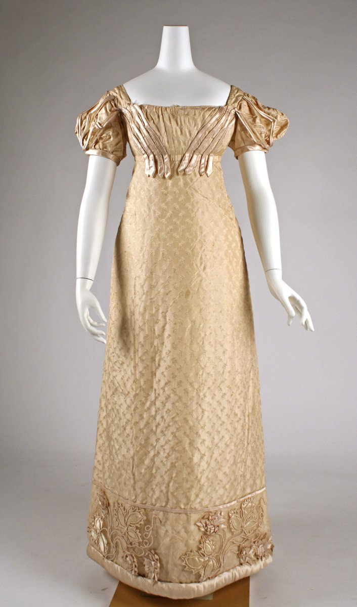 """A pale beige gown from 1822 with a square neck and puffy """"princess"""" sleeves. It still has a Regency-style silhouette, but the sleeves and dropping waist are moving away. The pattern is a small damask design, and the edges have a puffed, almost quilted quality. There is a motif of vines at the edges. Met museum."""