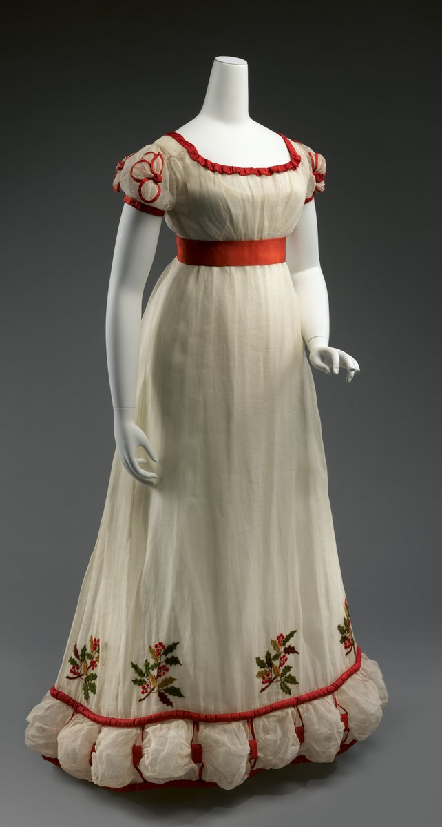 From the Met description: Fashionable British dress from the early decades of the nineteenth century reveals a fascination with historical styles. Drawing inspiration from literature, theater costumes, and history paintings of medieval and Renaissance subjects, dressmakers incorporated stylistic details from twelfth- through seventeenth-century dress into contemporary fashions. The decoratively slashed sleeves of the sixteenth century, through which linen undershirts were loosely drawn, inspired puffed trimmings such as the bouillons of fine white lawn that encircle the hem of this 1820s dress. Historicized elements such as these reflect a nostalgia for Britain's past, evoking romantic notions of the chivalry or patriotism of earlier eras. The wool crewel-embroidered holly boughs at the hem indicate that the dress was worn in winter, when the plant's berries and foliage provided welcome color and featured prominently in Christmas decorations.