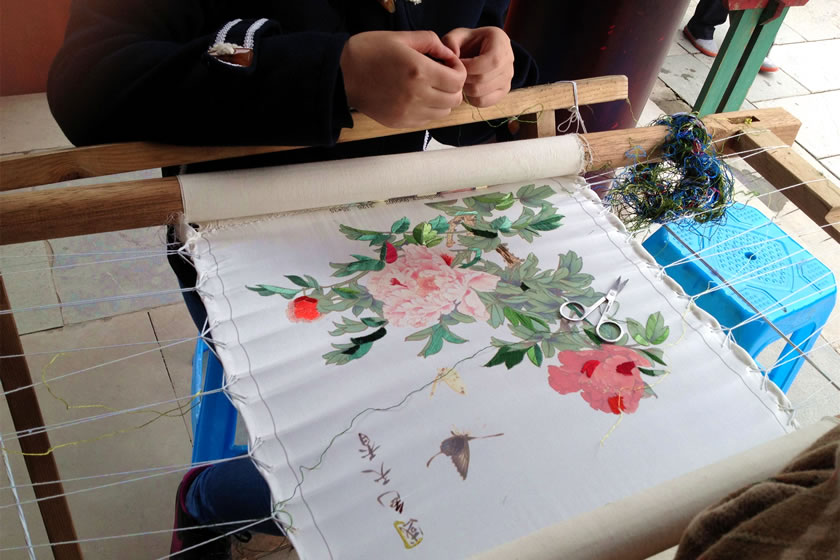 Closeup of embroidery from Sichuan Travel Guide  -- wooden dowels across a small loom and floral patterns. Via https://www.sichuantravelguide.com/chengdu/attractions/chengdu-shu-brocade-and-embroidery-museum.html