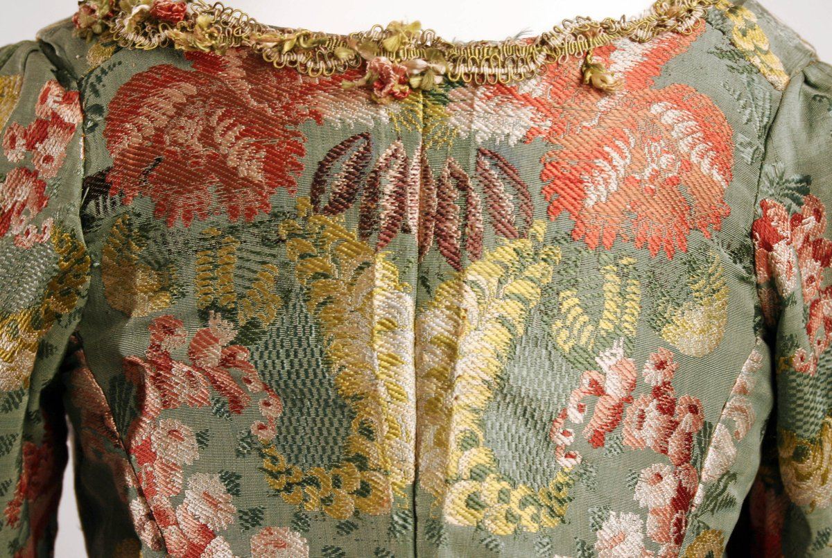 Detail from a brocade gown from 1774-93 Robe à la Polonaise via the Met Museum (Public Domain) -- clear details of floral patterns on a green background.
