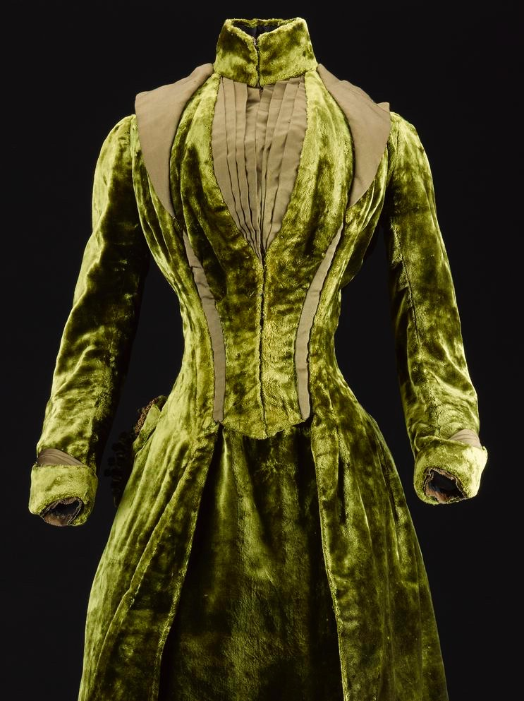 Green Velvet Dress - Image © National Museums Scotland Woman's dress, one of a two part ensemble, in dark green silk velvet, fastening at the front with a standing collar with lapels, bodice front and cuffs trimmed with dark green ribbed silk, full-length sleeves and the skirt shaped for a bustle at the back with a large self-material bow: British, Scottish, Edinburgh, by Gowan and Strachan, c.1885 - 1888