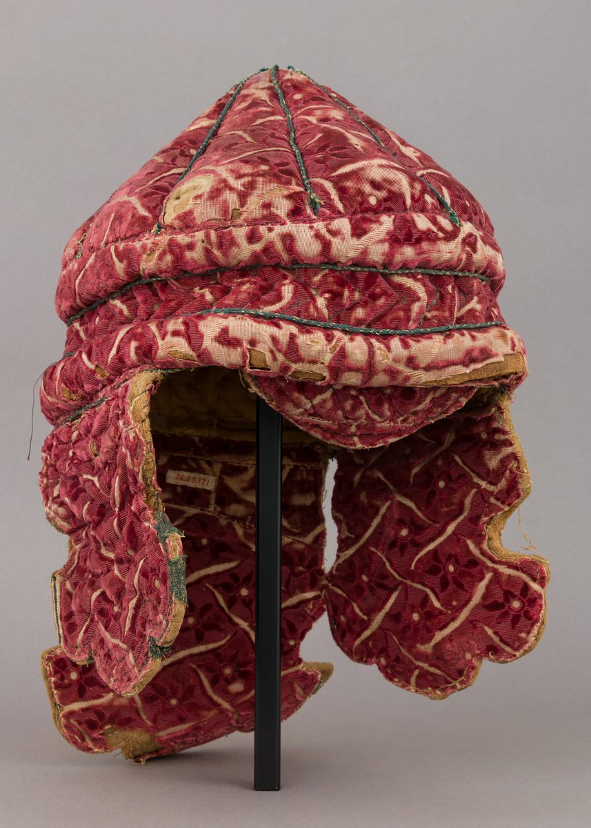 Helmet 18th century  Central Indian  Met museum - red velvet hat with long ear flaps and geometric designs that show wear and tear on the edges.