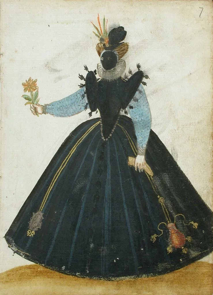 A woman wearing a visard and holding a flower.