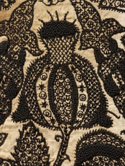 Embroidered top of a woman's smock, 1575-1585, English; blackwork, black silk embroidered on bleached linen, edged with black linen chain lace, reconstructed after acquistion. - V&A copyright - Closeup of Pomegranate.
