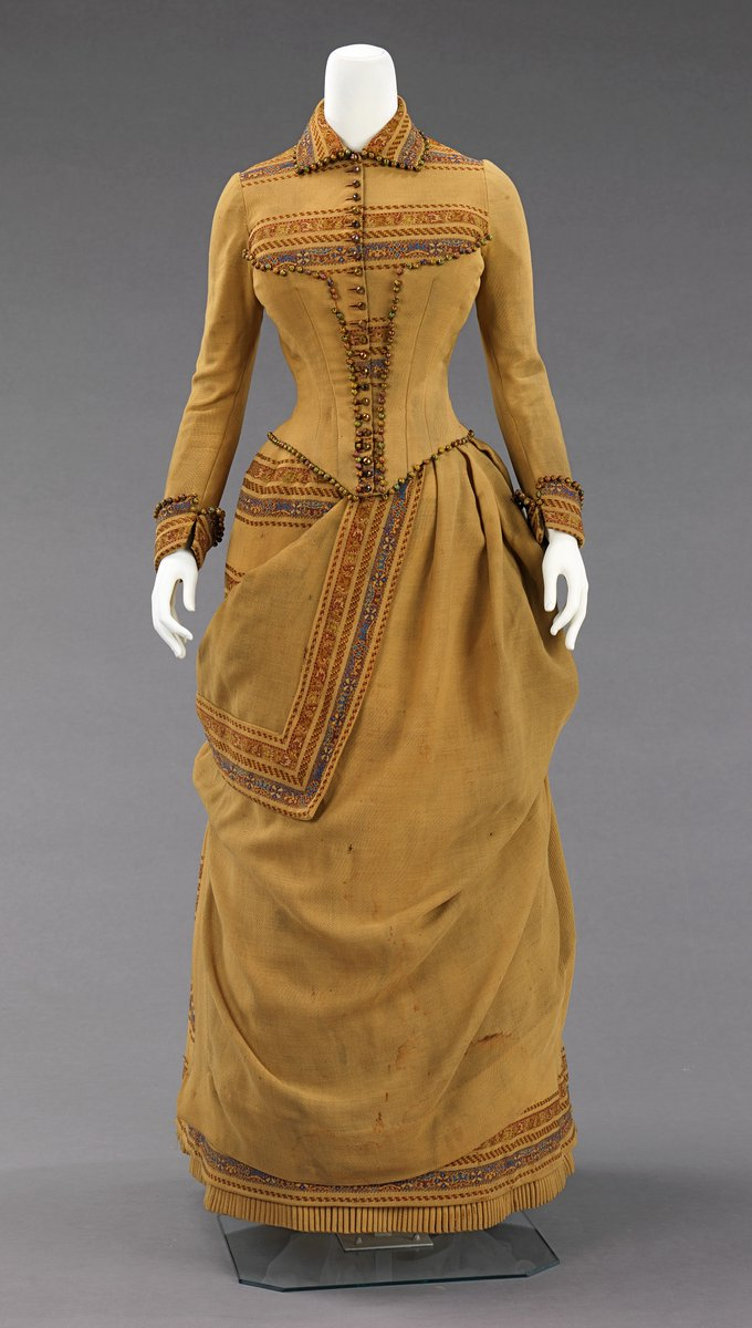 Ochre dress with false corset, geometric embroidery. Long sleeves, collar -- tiny waist! This dress belonged to Amelia Beard Hollenback (1844-1918), wife of the prominent financier and philanthropist John Welles Hollenback (1835-1927). In 1874, the Hollenback family settled in the neighborhood of Clinton Hill in Brooklyn. In the 19th century, Brooklyn became a metropolitan center with numerous affluent neighborhoods and a thriving downtown shopping district. Like many of the garments in Hollenback gift, this dress was most likely custom-made by a Brooklyn-based dressmaker. The unusual color and intriguing use of solid and striped wool fabric in this day dress has a folkloric aesthetic, which may have been inspired by an Amelia Hollenback's travels through the Southwest. The inventive asymmetrical draping shows a high level of sophistication and design sensibility that was atypical for a day dress. - The Metropolitan Museum of Art, Public Domain.