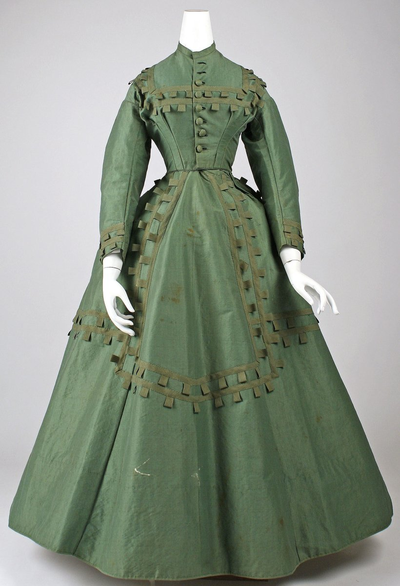 Dress 1864–65 - American. A green dress with long sleeves, a long, flared skirt, and squares at the apron and collar and chest in contrasting green. Big, fabric buttons on the bodice; the dress sleeves go to the wrists. Public domain - from the Met Museum.