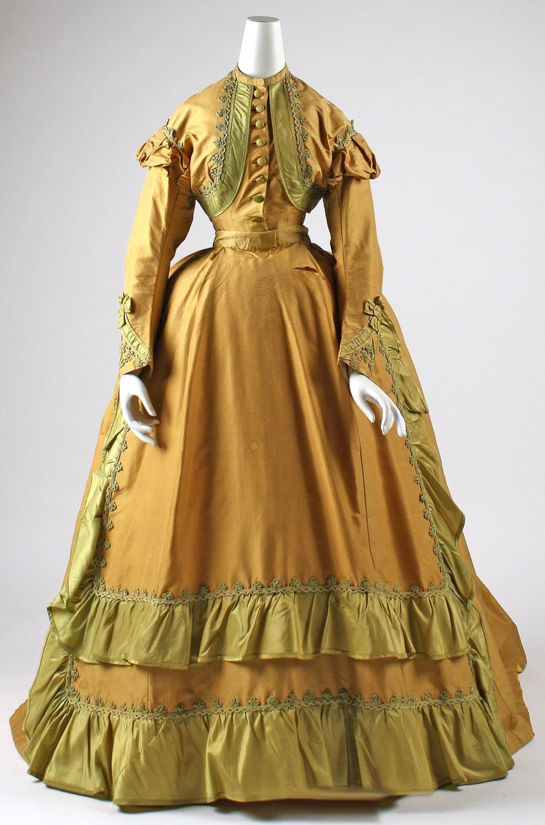 """Chatreuse and saffron colored gown from 1866; Met Museum, Public Domain.   """"A trompe l'oeil bolero jacket cropped and defined the bust, while the waist rose into the ribcage, genuinely above the zone of the waist. The devices of bolero and apron differentiated sectors within the dress and emphasized the high placement of the waist, while the crinoline hoop shifted to the back to make the great shape of the skirt mountainously prominent. Such monumental dress captured what French poet Charles Baudelaire called the """"pomp and circumstance"""" of modern urban life."""""""