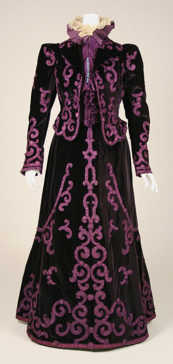 This is a walking suit in purple and deep mauve from the House of Paquin in the last 1890s. It has a slightly flared skirt and a fitted jacket with a ruff and collar. The whole dress has swirls and designs to accentuate the shape of the dress. Velvet.
