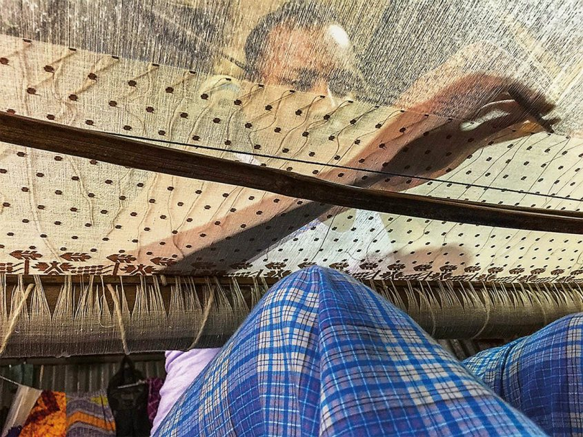 A weaver at a delicate loom, his hand transparent through the top of the ornately designed fabric.