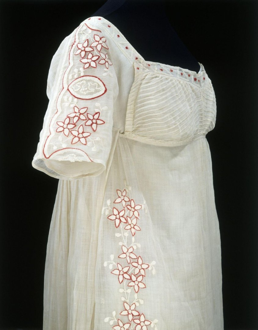 ©Victoria & Albert Museum, London - 1808 - This early nineteenth century muslin dress is embroidered with clusters of flowers and leaves. The embroidery is worked in satin stitch, chain stitch and French knots, the design trails down across the front of the dress and around the scalloped hemline to simulate a draped tunic-style garment slit up the side seam.  The front of the bodice is made up of a panel of bias-cut muslin, which is sewn onto the skirt rather like the bib of an apron so that it can be placed in position at the neck with pins. When the pins are removed the bib front falls away to reveal linen underflaps which fasten across the bust to give support. This type of bodice construction was common during this period in this style of dress and is known as the high stomacher front.