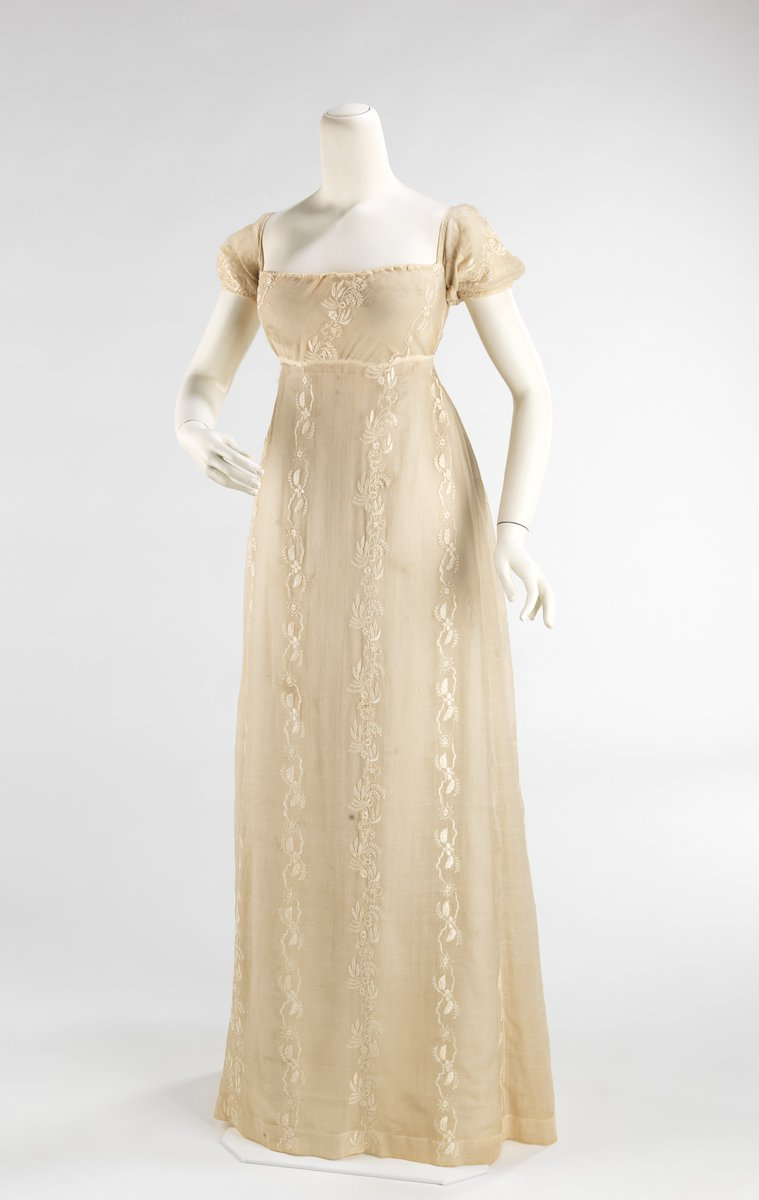 Met Museum - long, typical shift gown from the early 19th century with a high waist; pale ivory with embroidery, capped sleeves. Public domain.   Fine Indian muslin used in the Empire period was manufactured and embroidered in India and exported to Europe and America. The finest and most sheer cottons were coveted because for these qualities.