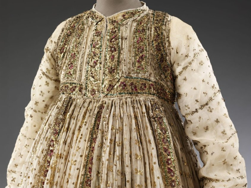18th - early 19th century muslin gown, made in India. A woman's gown. (c)Victoria and Albert Museum, London   Fine muslin ground with decoration in applied tinsel, spangles and foil. The peshwaz was made for a small wearer. The bodice portion is heavily embellished with wide bands of decoration around the sleeves, neck, hem, front-opening, and down the middle of the ground panels. The bands are made of silver-gilt, bordered by strips of green foil, with rows of blossoms in red foil and sequins. The same style of bands decorate the edges and hems of the skirt panels, and the wrists of the sleeves. The main ground of the sleeves and skirt is embellished with a motif of silver-gilt strip couched into four-pteal blossoms, regularly divided by serrated rows of silver-gilt foil. A deep striped trim lines the inside bottom hem of the skirt.