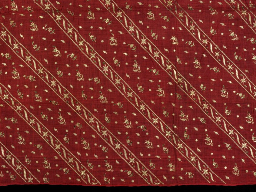 Closeup of muslin, (c)Victoria and Albert Museum, London - ca. 1855 (made), made in Chennai.  Red muslin textile, possibly a scarf, with diagonal bands of floral designs in flattened gold wire, gold-wrapped thread and green spangles.