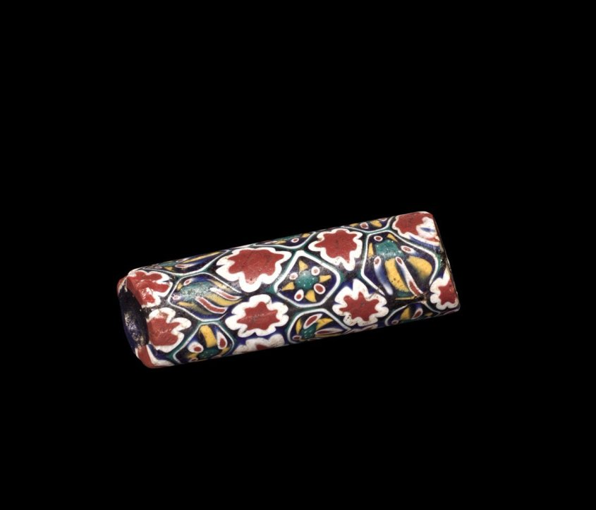 A single bead with a flower pattern, called Millefiori, made in Venice. Red flowers, green and yellow flowers, combine to make the telltale design. From the Corning Museum, dating from the 19th c.