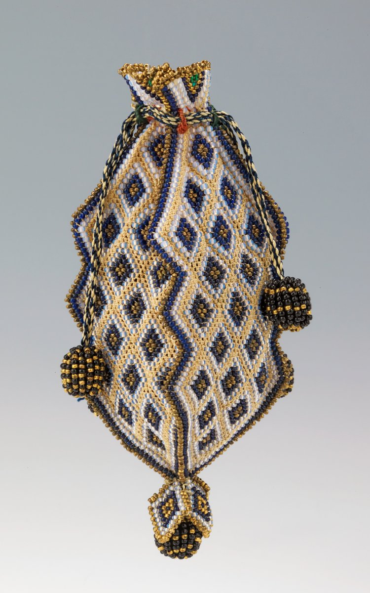 A reticule, or holding bag, with beaded motifs in diamonds. Yellow, gold, white, and blue, with big pompoms.  From the Met Museum, public domain.