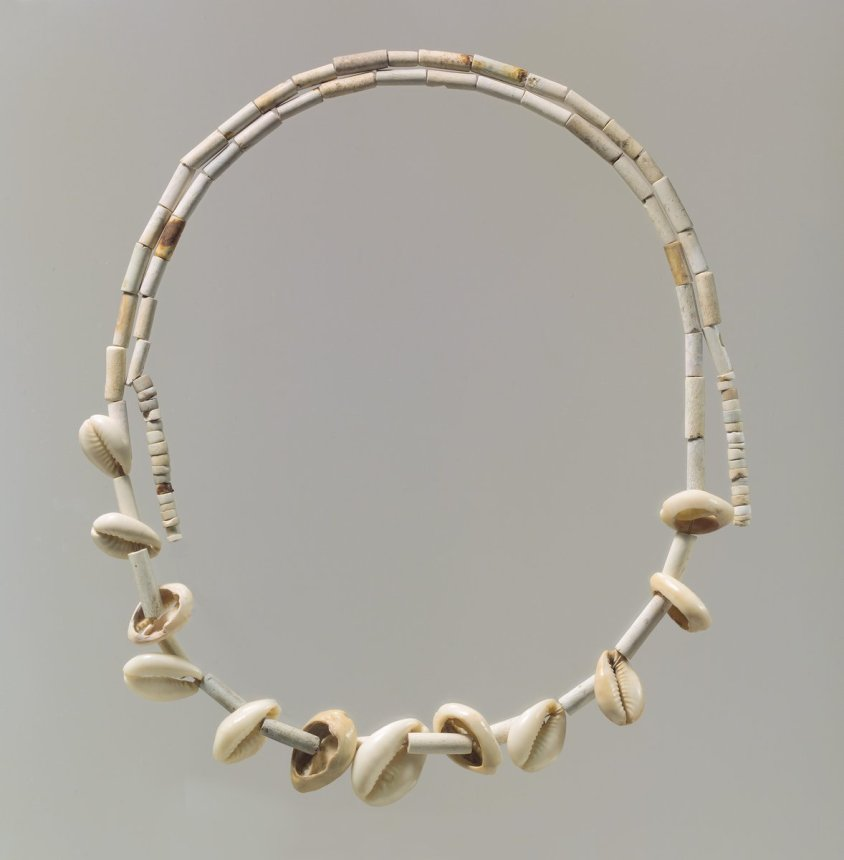Met Museum - Public domain - Three different types of beads have been strung together in this necklace: long tubular stone beads, smaller circular spacers, and cowrie shells. It is not known how the beads were originally worn in antiquity, since any string or other material that would have held them together has long since disintegrated. Beads were worn as jewelry and sewn to clothing as early as the Neolithic period in the ancient Near East.