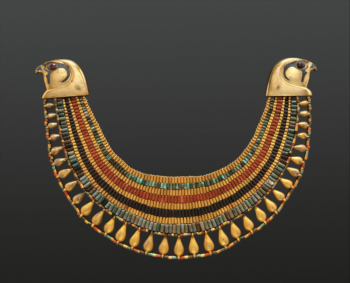 From the Met Museum, public domain. Nine rows of faience beads and other beadwork in gold, red, blue, grey, and yellow, flanked by two large falcon heads on each side in gold. The outermost row has openwork upon it. Still in impeccable condition in spite of its age.