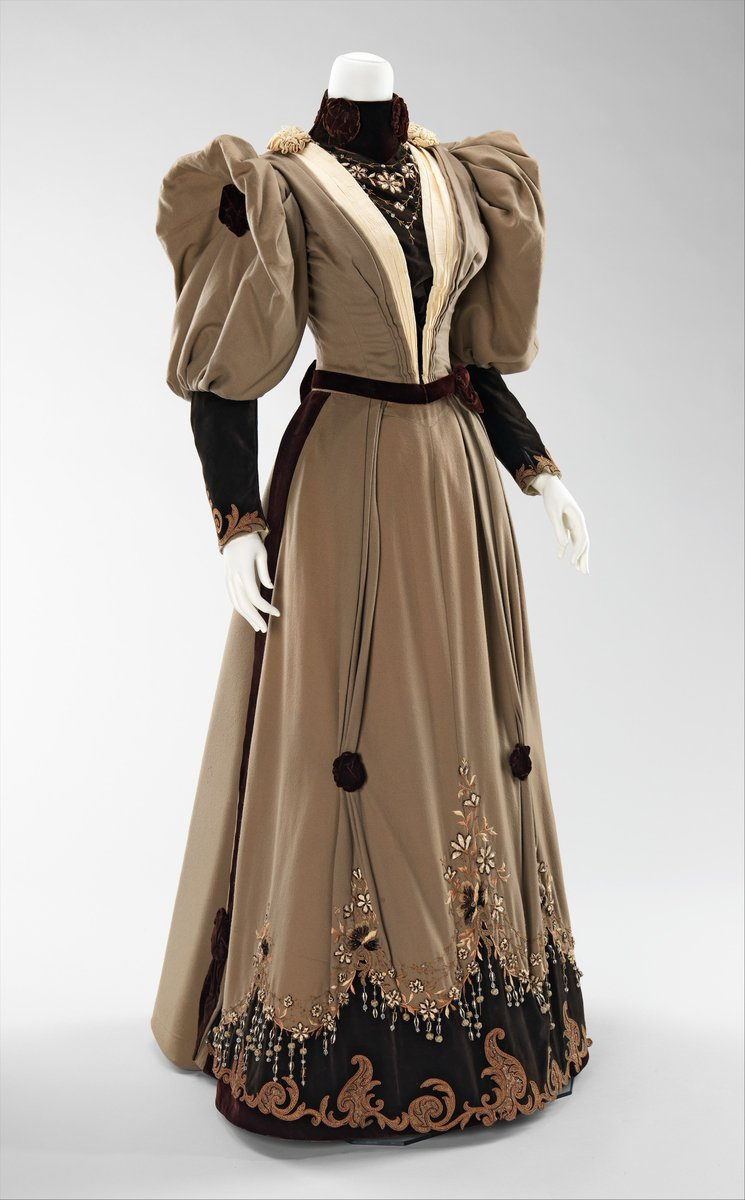 This is high style dress of the period when sleeves were getting larger with each season. The unique embroidery is distinctive and representative of the overt extravagance applied in this period. - A brown dress with big, puffy sleeves, a narrow waist, and lapels. Contrasted with a reddish brown velvet and puckered. Appliqué embroidery at the hem. Met Museum, public domain.