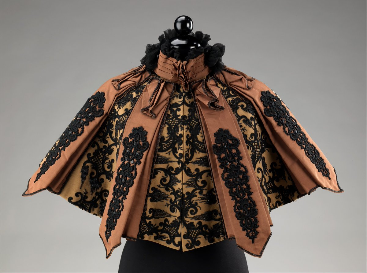 This beautifully constructed Pingat cape gains a rich and elegant appearance from its use of coordinating black beadwork embroidery on alternating flat and pleated panels of contrasting materials. That elegance can particularly be seen in the front where the embroidery on the two flannel panels line up to create a larger cohesive design oriented horizontally, as opposed to the other panels which are vertically oriented. - Met Museum, Public Domain.