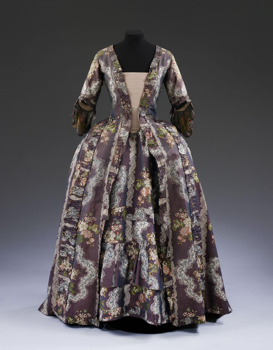 ©Victoria and Albert Museum, London - Made of shot silk faille, brocaded with multi-coloured bunches of flowers, a curvy stripe of lace, and a meander of lace and flowers. The decoration of the gown and petticoat - round the neck and down the front and skirt, and round the hem of the petticoat - is made of ruched bands of the same silk. Ground weft purple; warp pink. Brocading wefts: white, red, peach, two shades of blue, and three shades of green in silk floss, and white cordonnet (a tightly twisted silk thread). Internal lining and bodice are in sturdy, closely woven linen.