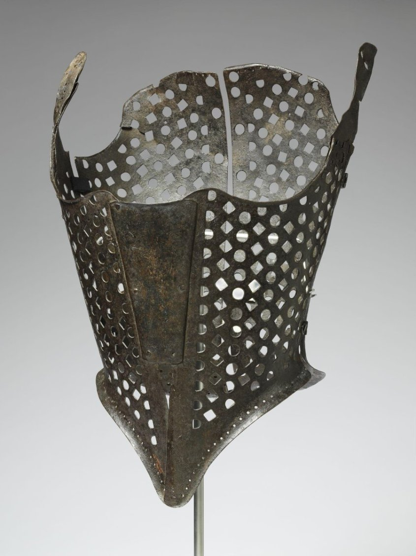 (c)Victoria and Albert Museum, London - Iron bodice, corset style, made from shaped pieces of metal, square and round cutouts creating a mesh effect. Hinged at sides. One side of corset detached. Lacing holes around lower edge of corset.
