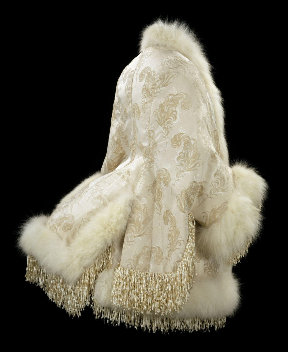 Dolman-sleeved jacket of cream silk voided velvet with a design of ostrich feathers, trimmed at the neck and front, cuffs and hems with white artic fox and a silk chenille fringe. Lined with machine-quilted satin.  ©Victoria and Albert Museum, London