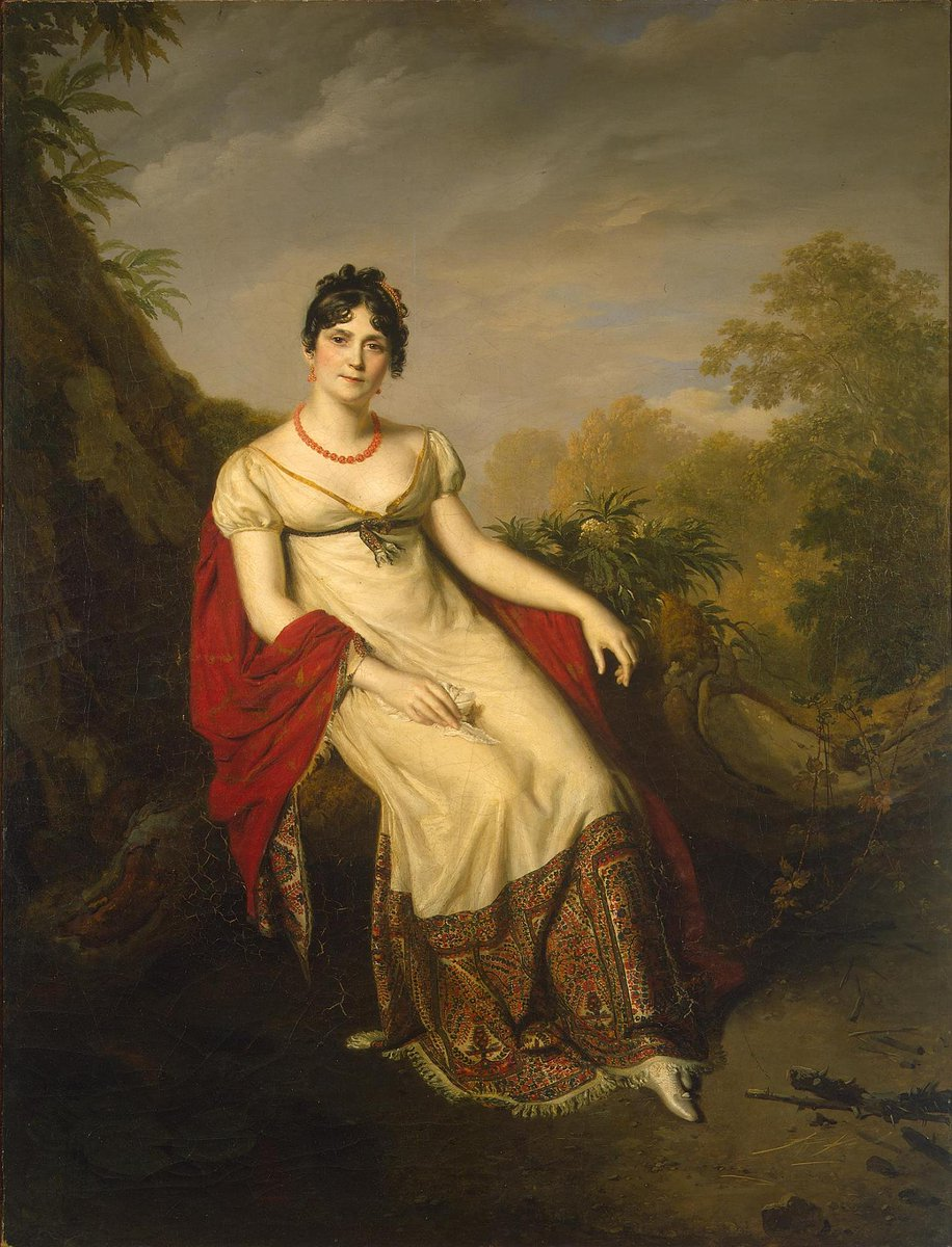 """Josephine de Beauharnais reclining in a post wearing a red velvet cape (that looks like it might have some boteh on it) with a typical muslin """"empire waist"""" dress hemmed in additional pashmina style fabric. Ca. early 1800s, public domain."""
