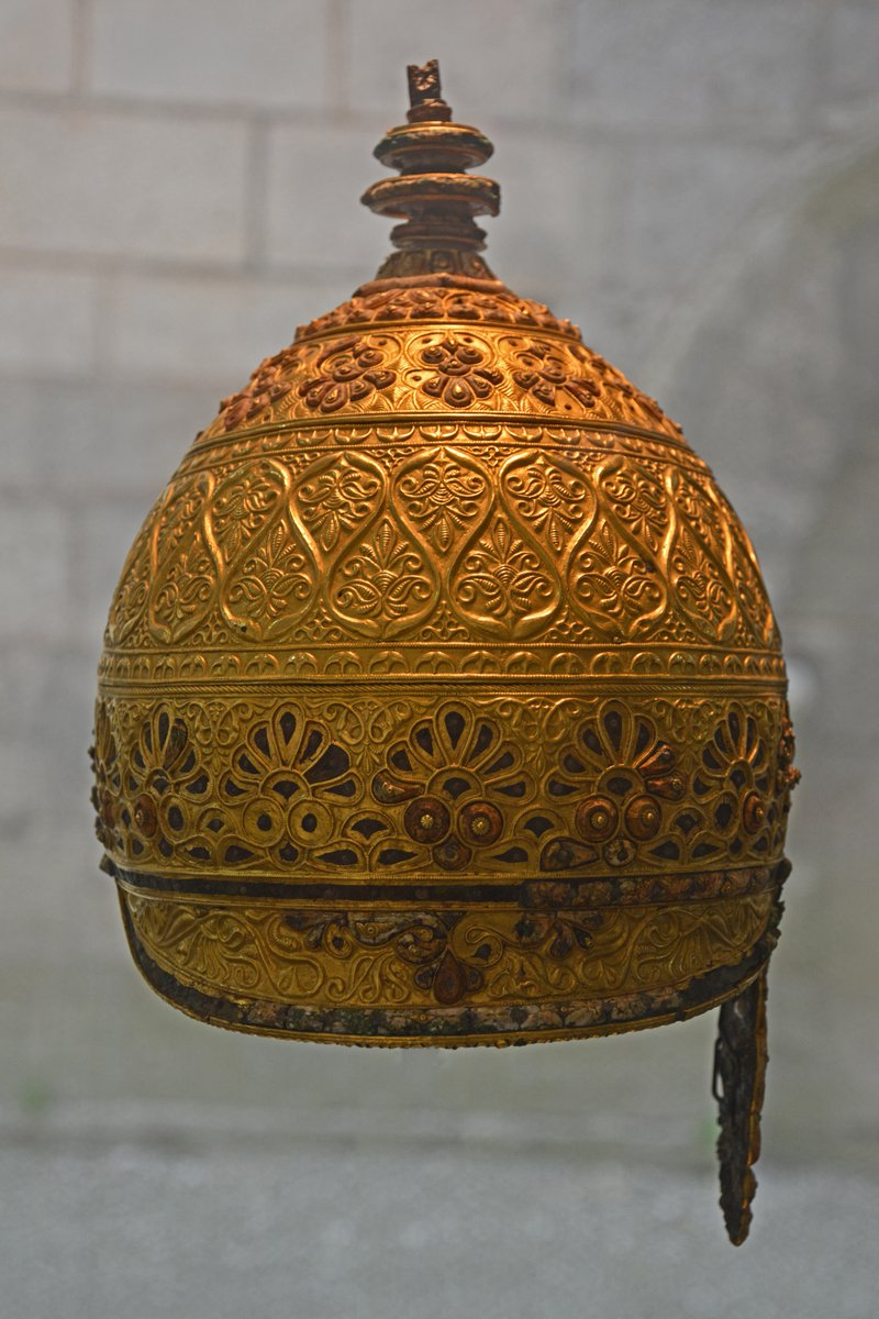 """A helmet from Bronze Age France with layers of elaborate design culminating at a peak. Some of the designs on it look very like paisley or boteh """"leaves"""". Wikimedia Commons."""