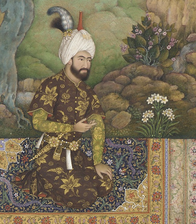 Shah Tahmasp (1514-1576)  wearing a brown and gold robe with boteh designs, and a feather that is the same iconic shape. He is sitting on an orange rug and wears a white turban; he has a beard, and a jeweled dagger, and behind him are flowers and trees. Image: Wikimedia commons.