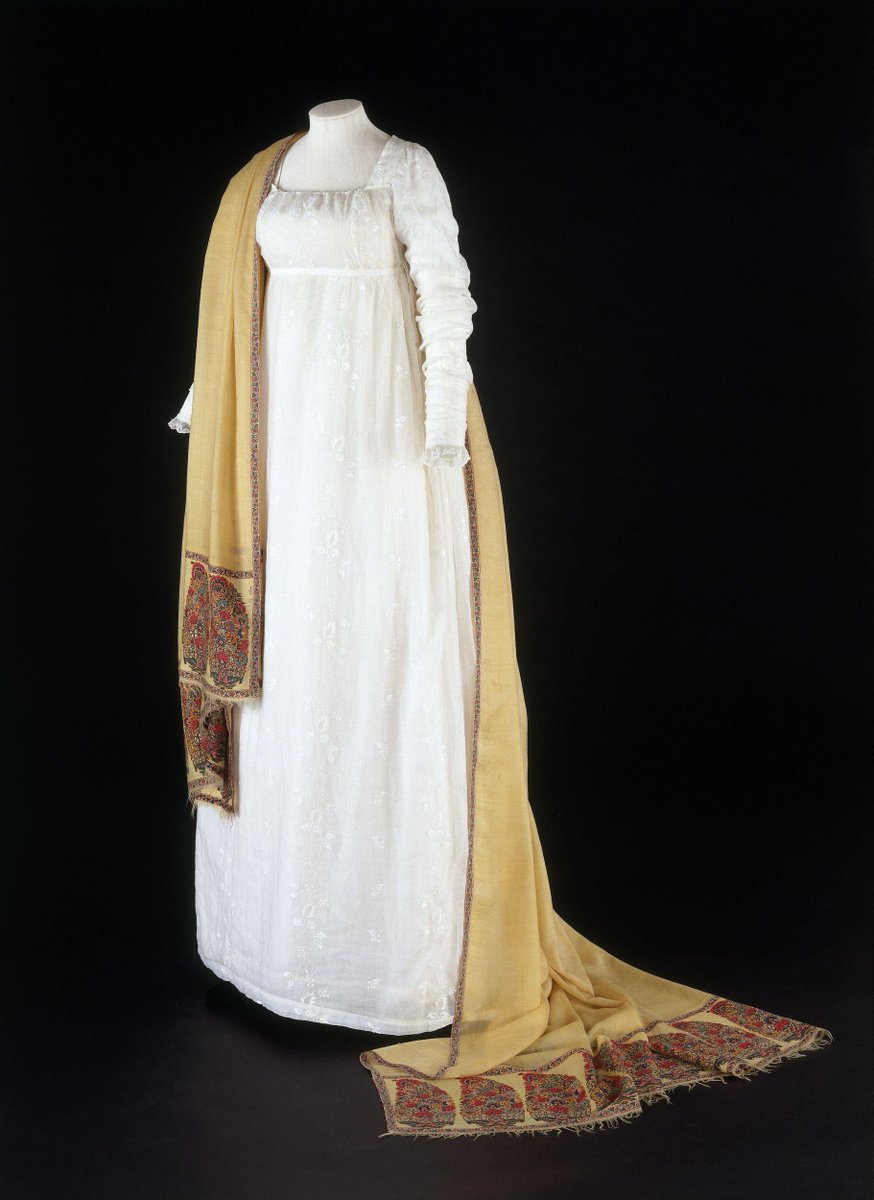 A classic white muslin gown from the Regency period with a bright saffron shawl over it, hemmed in red and green and blue paisley (boteh) pattern. This classic combination was all the rage during Jane Austen's time. ©Victoria and Albert Museum, London