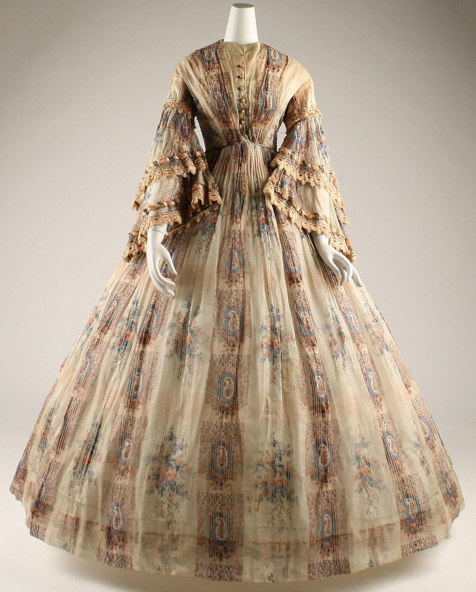 A typical 1850s silhouette with a huge skirt, bell sleeves, and an odd mix of floral and paisley motifs. It is very sheer and gauzy. This dress incorporates the romance of the buta motif in a fabric that has no similarity to the original Kashmir wool. The endemic Paisley-wool ligature is dissociated in the West, chiefly because of its extraordinary popularity as it becomes a design motif for all seasons.  Met Musuem, Public Domain.