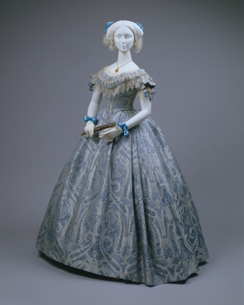 A classic Victorian mid-19th century ballgown with a pale blue silk fabric of paisleys and a ruffled lace top. Met Museum, public domain.