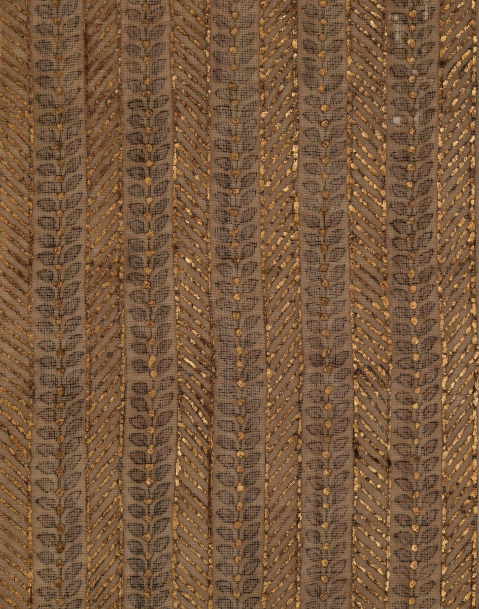 ©Victoria & Albert Museum, London - Fragment of cotton (muslin) with a vertical striped design of paired red leaves on stems outlined in dark violet. Gold leaf detailing applied with gum in pattern of striped bands and spots.
