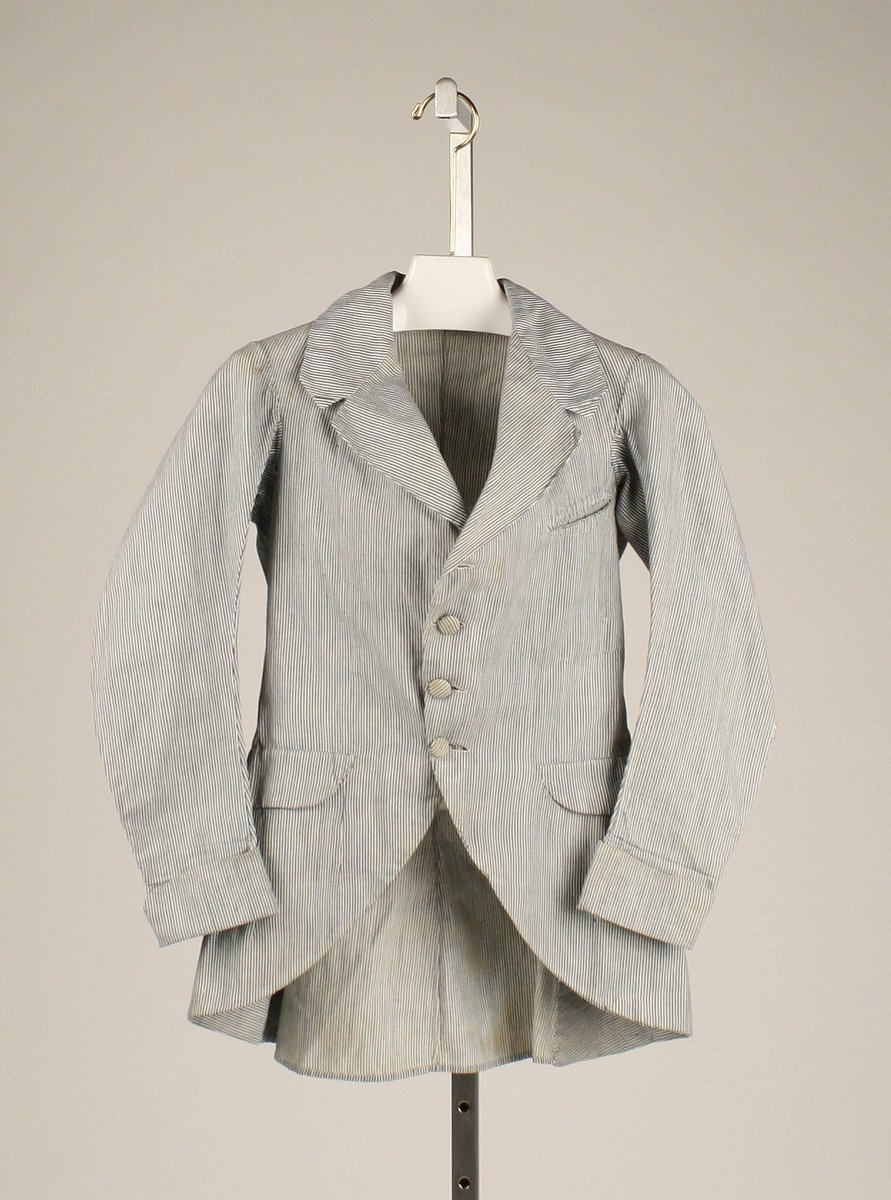 A seersucker frock coat in a classic, three-button suit. A summer frock coat of this kind assumes the same cut as a wool coat, distilling at this time into black or gray, for winter. - Met Museum, Public Domain.