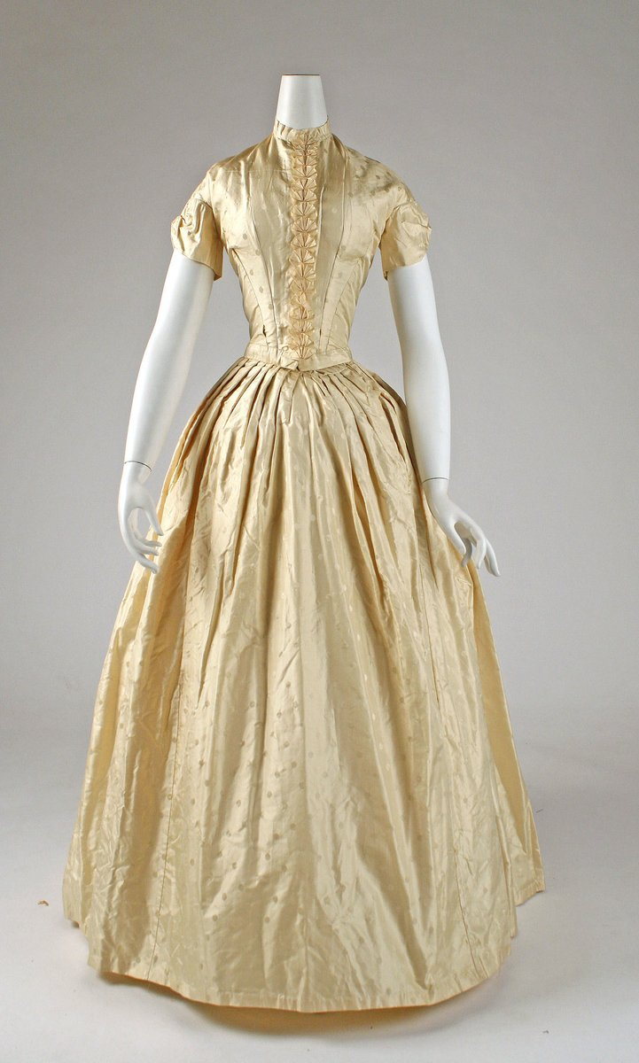 A pale gown of light cream, with short cap sleeves, a very narrow wait, and a line of pleated bows. High collar, billowy skirt, rather than sleeves.